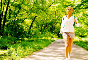 Young woman working out on a forest path.